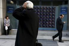 Un hombre mira un tablero electrónico que muestra índices de mercado, en una correduría en Tokio, Japón. 2 de marzo de 2016. Las bolsas de Asia subían el martes tras un comienzo vacilante de la sesión, extendiendo un repunte por las expectativas cada vez mayores de que los votantes británicos optarán por permanecer en la Unión Europea en el referendo de esta semana. REUTERS/Thomas Peter/Files