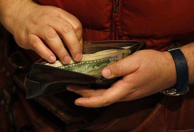A customer opens his wallet at a Macy's cash register on Black Friday in New York November 26, 2010.  REUTERS/Jessica Rinaldi
