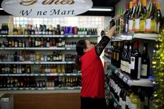 A staff checks on bottles of wine at a supermarket, in Shanghai, China, June 2, 2016. REUTERS/Aly Song