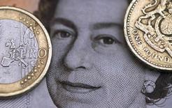 La libra esterlina se apreció el jueves a su máximo nivel de 2016 y el euro avanzaba contra el dólar y el yen, después de que una serie de sondeos indicaron que Reino Unido que se inclinará por permanecer en la Unión Europea. En la imagen, una moneda de dos euros y una libra encima de un retrato de la reina Isabel II de Inglaterra, el 16 de marzo de 2016.  REUTERS/Phil Noble/Illustration/