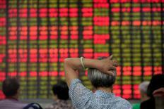 Inversores miran una pantalla electrónica que muestra información bursátil, en una correduría en Shanghái, China. 23 de junio de 2016. La libra esterlina se afirmaba y las bolsas de Asia subían en medio de un comercio cauteloso el jueves, mientras muchos inversores buscaban refugio en activos seguros como el yen mientras se preparan para una votación que decidirá si Reino Unido continúa en la Unión Europea. REUTERS/Aly Song