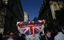 """Las bolsas europeas se hundían más de un ocho por ciento el viernes, lideradas por el sector bancario, y se encaminaba hacia su mayor caída porcentual diaria después de que los británicos votasen a favor de abandonar la Unión Europea en un referéndum. En la imagen, un votante sostiene una bandera británica con el lema """"Vota salir"""", el 24 de junio de 2016 en Londres. REUTERS/Neil Hall"""
