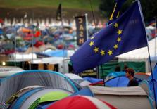 A reveller stands in front of a tent with the European Union flag at Worthy Farm in Somerset during the Glastonbury Festival, Britain June 23, 2016. REUTERS/Stoyan Nenov