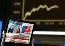 Телеэкран на фоне графика DAX на фондовой бирже во Франкфурте-на-Майне. 24 июня 2016 года. Привыкшие к работе в кризисных условиях российские трейдеры без паники встретили шокирующие итоги референдума о выходе Британии из ЕС, которые заставили невыспавшихся европейских игроков распродавать активы по всему миру. REUTERS/Ralph Orlowski