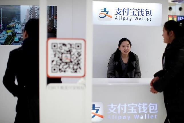 A sales assistant sits behind and under Alipay logos at a train station in Shanghai, February 9, 2015. REUTERS/Aly Song/File Photo