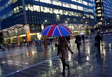 Trabajadores caminan bajo la lluvia en el distrito financiero de Canary Wharf, en Londres, Gran Bretaña. 11 de noviembre de 2013. La votación británica a favor de que el país abandone la Unión Europea generaba nuevas turbulencias en los mercados financieros el lunes, a pesar de los esfuerzos de los líderes del Reino Unido por poner fin a la profunda incertidumbre política y económica que generó el resultado del referendo. REUTERS/Eddie Keogh/File Photo