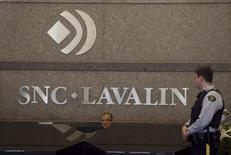 A Royal Canadian Mounted Police (RCMP) officer looks at a receptionist at the headquarters of SNC Lavalin in Montreal in this file photo dated April 13, 2012. REUTERS/Christinne Muschi