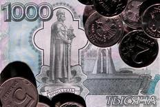 Тысячерублевая банкнота и монеты. Рубль в плюсе вечером среды, получив поддержку от нефти, ускорившей позитивную динамику после новостей о снижении её запасов в США, при этом сокращение предложения экспортной выручки по завершении налогового периода могло компенсироваться корпоративными продажами валюты к предстоящей уплате рублевых дивидендов.  REUTERS/Maxim Zmeyev/Illustration