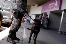A soldier of the military police battalion and his dog take part in an instructional exercise with officers of an elite unit of the French police, who is responsible for anti-terrorist actions in France, at Terminal 1 of the Tom Jobim International Airport in Rio de Janeiro, Brazil, May 25, 2016. REUTERS/Ueslei Marcelino