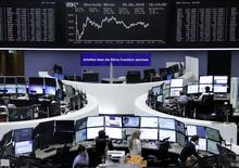 Traders work at their desks in front of the German share price index, DAX board, at the stock exchange in Frankfurt, Germany, June 30, 2016.     REUTERS/Staff/Remote