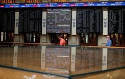 El Ibex-35 afianzaba el tono alcista a media sesión tras un inicio titubeante el viernes, siguiendo la tendencia de otras plazas europeas y asiáticas ante la perspectivas de que los bancos centrales introduzcan nuevas medidas de alivio en su política monetaria. En la imagen, pantallas electrónicas en la Bolsa de Madrid, el 24 de junio de 2016.  REUTERS/Andrea Comas