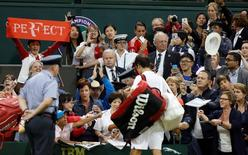 Britain Tennis - Wimbledon - All England Lawn Tennis & Croquet Club, Wimbledon, England - 1/7/16 Switzerland's Roger Federer signs his autograph for fans after winning his match against Great Britain's Daniel Evans REUTERS/Paul Childs