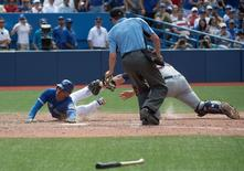 Jul 2, 2016; Toronto, Ontario, CAN; Toronto Blue Jays left fielder Ezequiel Carrera (3) slides into home plate scoring a run ahead of the tag from Cleveland Indians catcher Chris Gimenez (38) during the eighth inning in a game at Rogers Centre. The Toronto Blue jays won 9-6. Mandatory Credit: Nick Turchiaro-USA TODAY Sports