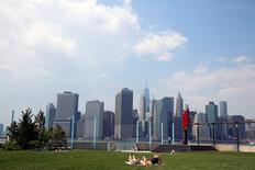 The skyline of lower Manhattan is seen as people lay on the grass in Brooklyn Bridge Park in the Brooklyn borough of New York City, U.S., May 27, 2016. REUTERS/Brendan McDermid