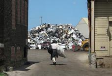 Сборщик лома идет к груде металла на складе в Милуоки, Висконсин. Эрика каждый день по четыре часа бродит по улицам Милуоки, роется в мусоре и набивает свою красную пластиковую тележку из супермаркета алюминиевыми банками и другими металлическими предметами, которые потом продает в попытке прокормить троих детей.  REUTERS/Brendan O'Brien - RTX2JLUZ
