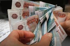 Сотрудник магазине пересчитывает деньги. Россия израсходует остаток Резервного фонда в 2017 году и начнет тратить Фонд национального благосостояния, который за три года сократится почти на 1,75 триллиона рублей, одновременно в четыре раза увеличив заимствования на внутреннем рынке, чтобы свести концы с концами.   REUTERS/Ilya Naymushin (RUSSIA - Tags: BUSINESS)