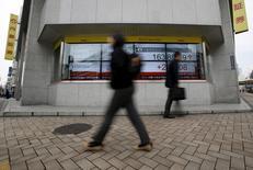 Peatones caminan cerca de una pantalla electrónica que muestra información bursátil, en Tokio, Japón. 29 de febrero de 2016. Las bolsas de Asia cortaban el martes una racha de cinco días de avances luego de que los inversores recogieron ganancias, pese a las expectativas de un mayor estímulo de los bancos centrales para contrarrestar la decisión de Reino Unido de dejar la Unión Europea. REUTERS/Yuya Shino