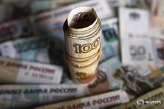 Рублевые банкноты различного достоинства. Рубль готовится завершить ростом пятничные торги и показать лишь незначительное снижение по итогам недели, невзирая на существенное недельное падение нефтяных цен - на его стороне выступал фактор дивидендных выплат в РФ, под которые корпорации-экспортеры продают летом валютную выручку. REUTERS/Kacper Pempel