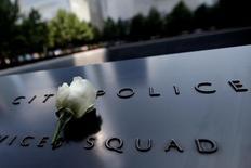 Белая роза на мемориальной доске в Нью-Йорке в память о полицейских, погибших 9 сентября 2001 года во время атаки захвативших лайнеры смертников. Фото от 8 июля 2016 года. Пятеро полицейских в техасском Далласе погибли от пуль как минимум одного снайпера, сообщил в пятницу потрясенный шеф городской полиции, указав на расовую подоплеку нападения в разгар президентской кампании в США. REUTERS/Mike Segar