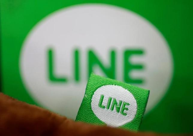 The logo of free messaging app Line is pictured on a smartphone and the company's stuffed toy in this photo illustration taken in Tokyo, Japan, September 23, 2014. REUTERS/Toru Hanai/Illustration/File Photo