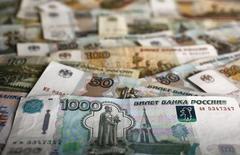 """Рублевые банкноты различного достоинства. Рубль был стабилен на торгах понедельника, поскольку снижение нефти на двухмесячные минимумы компенсировалось корпоративными продажами валюты под дивиденды и налоги, а также денежными потоками, связанными с приватизацией. Свою роль мог играть и фактор """"летнего трейдинга"""". REUTERS/Kacper Pempel"""