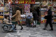 Una mujer pasea frente a una tienda con carteles de descuentos en el distrito comercial de Tokio, Japón, el 25 de febrero de 2016. El Gobierno de Japón reducirá su pronóstico de inflación al consumidor para el ejercicio en curso y ofrecerá una previsión para el año fiscal 2017 mucho menor que el objetivo del banco central de un 2 por ciento, dijeron el martes fuentes gubernamentales a Reuters. REUTERS/Yuya Shino