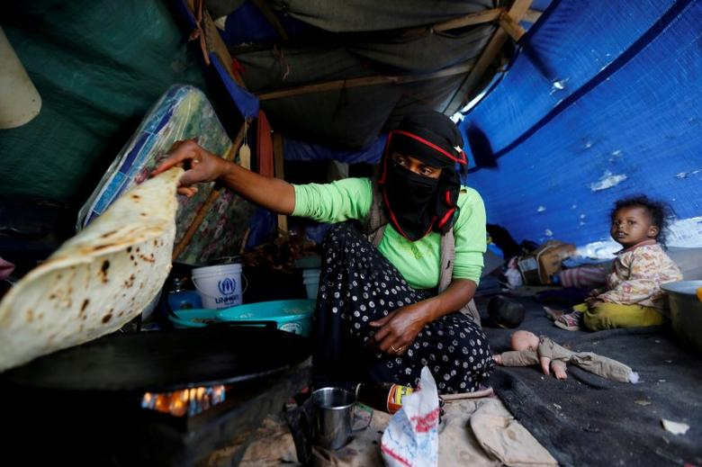 A woman makes bread inside her tent at a camp for internally displaced people near Sanaa, Yemen, May 24, 2016. REUTERS/Khaled Abdullah/File Photo