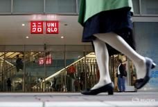 Пешеход проходит мимо магазина Uniqlo в Токио 6 апреля 2016 года. Fast Retailing, оператор магазинов одежды Uniqlo, в четверг отчитался о росте операционной прибыли в третьем квартале финансового года на 18,6 процента, чему способствовали хорошие продажи в онлайн-магазинах на внутреннем рынке, в Японии, и улучшение показателей в США. REUTERS/Yuya Shino/Files