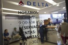 Клиенты в офисе Delta в Каракасе. Американская авиакомпания Delta Air Lines Inc отчиталась в четверг о превысившей ожидания прибыли во втором квартале и сообщила о намерении сократить количество мест, доступных для пассажиров в Великобритании и других странах, еще больше, чем планировалось осенью, чтобы избежать падения цен на авиабилеты.  REUTERS/Carlos Garcia Rawlins