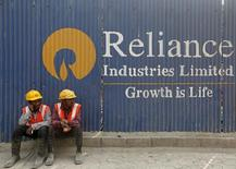 Labourers rest in front of an advertisement of Reliance Industries Limited at a construction site in Mumbai, India, March 2, 2016.  REUTERS/Shailesh Andrade
