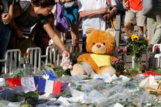 A woman places a stuffed toy alongside flowers, flags and a large stuffed toy in tribute to victims, two days after an attack by the driver of a heavy truck who ran into a crowd on Bastille Day killing scores and injuring as many on the Promenade des Anglais, in Nice, France, July 16, 2016.  REUTERS/Pascal Rossignol
