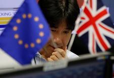 Валютный трейдер на бирже в Токио и флаги ЕС и Великобритании. 24 июня 2016 года. С выходом Великобритании из ЕС настало время для инвестиций в ее экономику, сказал глава японской телекоммуникационной корпорации SoftBank, покупающей британского разработчика чипов ARM Holdings  за $32 миллиарда. REUTERS/Issei Kato