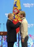 Russian President Vladimir Putin (L) awards Olympics team figure skating gold medal winner Yevgeny Plushenko at a ceremony in Sochi February 24, 2014. Russian President Vladimir Putin told the athletes who took the host nation to the top of the medals table at the Sochi Winter Olympics that they had accomplished their mission. REUTERS/Mikhail Klimentyev/RIA Novosti/Kremlin (RUSSIA - Tags: POLITICS SPORT OLYMPICS FIGURE SKATING) ATTENTION EDITORS - THIS IMAGE HAS BEEN SUPPLIED BY A THIRD PARTY. IT IS DISTRIBUTED, EXACTLY AS RECEIVED BY REUTERS, AS A SERVICE TO CLIENTS - RTX19EJU