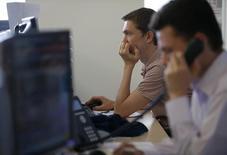 Трейдеры работают на Московской фондовой бирже. Снижение российских акций усилилось во второй половине торгов вторника в отсутствие какого-то определенного триггера, и участники рынка, отмечая поток неблагоприятных новостей, все же считают их поводом, а причиной - назревшую коррекцию цен после роста.  REUTERS/Sergei Karpukhin