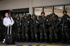 A passenger waits as Brazilian Air force soldiers patrol the Tom Jobim International airport ahead of the 2016 Rio Olympics in Rio de Janeiro, Brazil, July 19, 2016. REUTERS/Ueslei Marcelino