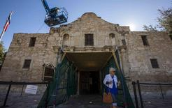 A woman walks past as men use a lift to repair and restore stonework along the curved facade of the Alamo in San Antonio, Texas October 26, 2015. REUTERS/Adrees Latif/File Photo