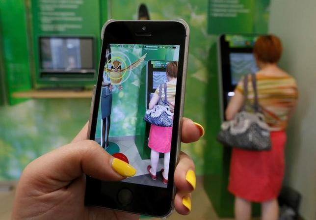 A woman plays the augmented reality mobile game ''Pokemon Go'' by Nintendo, as a visitor uses an automated teller machine (ATM) at a branch of Sberbank in central Krasnoyarsk, Siberia, Russia, July 20, 2016. REUTERS/Ilya Naymushin