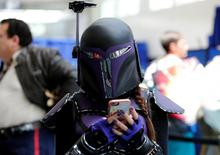 An attendee keeps tabs on her cell phone as she walks the convention floor at Comic-Con. REUTERS/Mike Blake