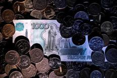 Рублевые банкноты и монеты. Рубль ушел в минус вечером относительно спокойной биржевой сессии понедельника за счет давления нефтяного рынка, где марка Brent упала под отметку $45 за баррель, что перебило поддержку российской валюте от внутридневных экспортных продаж к налогам и дивидендам. REUTERS/Maxim Zmeyev/Illustration
