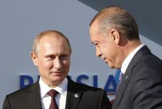 Президент России Владимир Путин 9слева) приветствует турецкого коллегу Тайипа Эрдогана на саммите G20 в Санкт-Петербурге 5 сентября 2013 года. Окончание ссоры между Москвой и Анкарой из-за сбитого российского бомбардировщика, о котором в конце июня объявил Кремль, сославшись на извинения президента Турции, будет отмечено в начале августа встречей Реджепа Тайипа Эрдогана с президентом Владимиром Путиным. REUTERS/Grigory Dukor