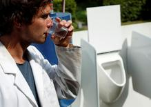 Belgian scientist Sebastiaan Derese drinks water from a machine that turns urine into drinkable water and fertilizer using solar energy, at the University of Ghent, Belgium, July 26, 2016. REUTERS/Francois Lenoir