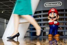 """A woman walks past a figure of """"Mario"""", a character in Nintendo's """"Mario Bros."""" video games, at a Nintendo centre in Tokyo July 29, 2015.  REUTERS/Thomas Peter/File Photo"""