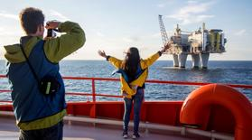 People observe an oil platform during a cruise in the North Sea, Norway, in this handout picture July 21, 2016. Picture taken July 21, 2016. Thomas Mortveit/ Edda Accommodation/Handout via Reuters