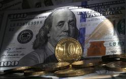 Десятирублевые монеты на фоне купюры в 100 долларов. Рубль дешевеет утром пятницы в условиях низких нефтяных цен, обновляющих трехмесячные минимумы, а также после завершения налогового периода, сдерживать рыночную активность могут ожидания совета директоров ЦБР, который, как предполагается, сохранит текущий уровень ключевой ставки 10,50 процента.  REUTERS/Alexander Demianchuk