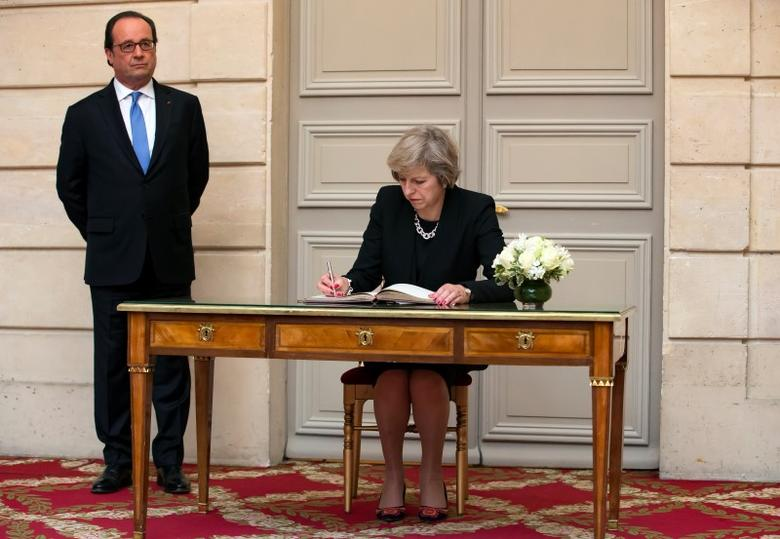 French President Francois Hollande (L) stands near as Britain's Prime Minister Theresa May signs a register after their meeting at the Elysee Palace in Paris, France, July 21, 2016.  REUTERS/Ian Langsdon/Pool