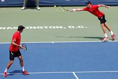 Aug 9, 2015; Washington, DC, USA; Mike Bryan attempts to hit forehand as partner Bob Bryan looks on against Ivan Dodig and Marcelo Melo (both not pictured) in the men's doubles final of the 2015 Citi Open at Rock Creek Park Tennis Center. The Bryans won 6-4, 6-2. Mandatory Credit: Geoff Burke-USA TODAY Sports