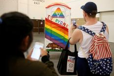 """People take a picture of a portable toilet art project protesting the North Carolina HB 2 bathroom bill during the """"Politicon"""" convention in Pasadena, California, U.S. June 25, 2016.  REUTERS/Patrick T. Fallon"""