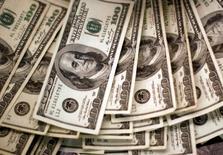 Стодолларовые купюры. Доллар в понедельник отодвинулся от минимумов, зафиксированных после выхода разочаровывающих данных о росте ВВП США на прошлой неделе, в то время как иена восстановила часть крупных потерь, понесенных после того, как Банк Японии объявил о значительно менее решительных, чем ожидалось, мерах стимулирования.  REUTERS/Rick Wilking/File Photo