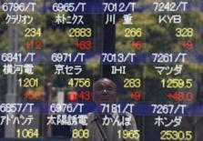 Un hombre se refleja en una pantalla que muestra información bursátil, en Tokio, Japón. 11 de julio de 2016. Las acciones asiáticas alcanzaron el lunes un máximo de un año luego de que los decepcionantes indicadores de crecimiento económico en Estados Unidos redujeron las expectativas de que la Reserva Federal eleve las tasas de interés del país en los meses venideros. REUTERS/Issei Kato