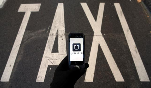 The logo of car-sharing service app Uber on a smartphone over a reserved lane for taxis in a street is seen in this photo illustration taken December 10, 2014.   REUTERS/Sergio Perez/Illustration/File Photo - RTSKHW2